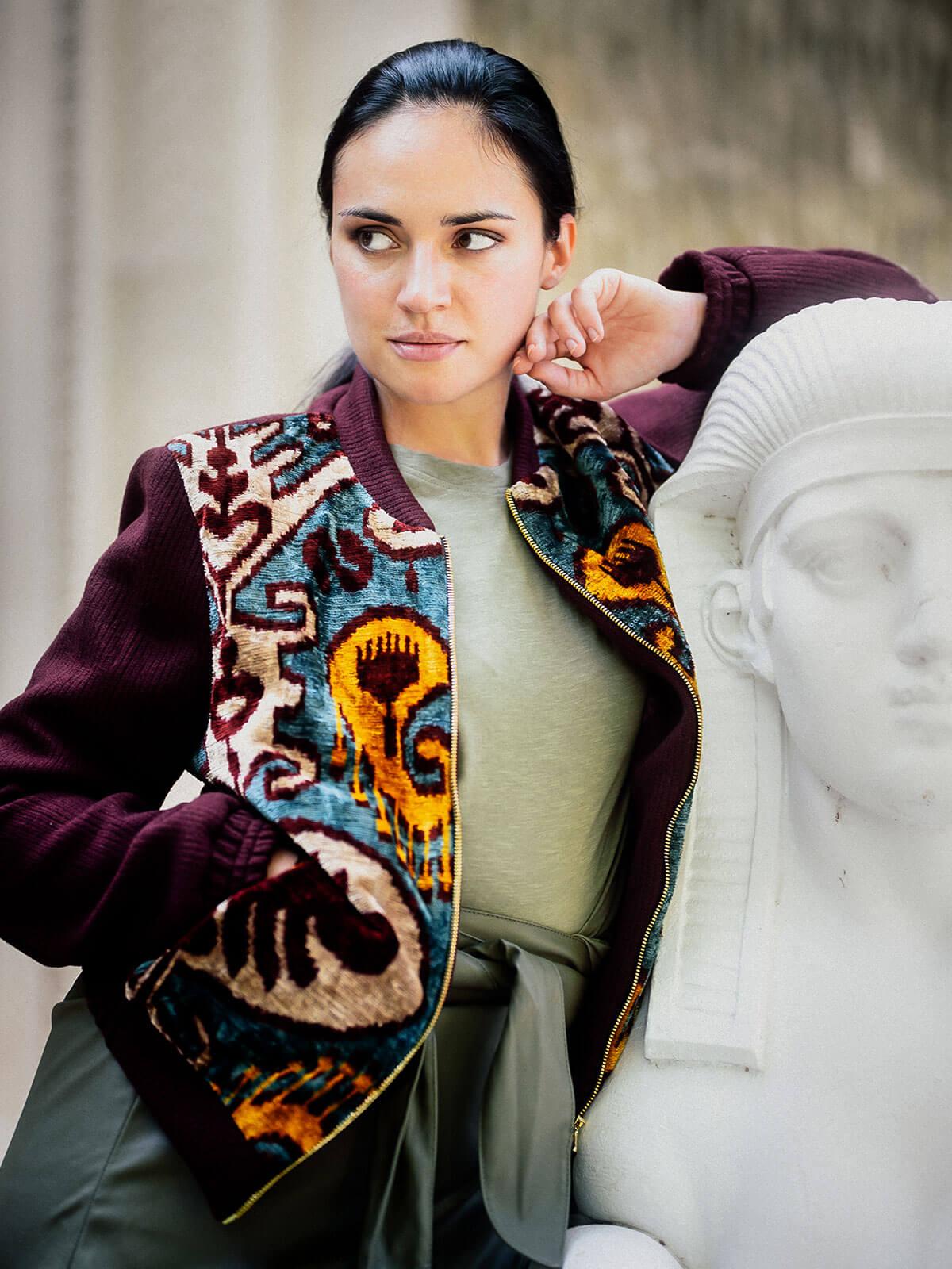 Junge Frau steht angelehnt an eine Statue in einer gemusterten Bomberjacke