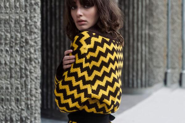 junge Frau im Cardigan aus Wolle in Ikatoptik gelb und braun geschneidert