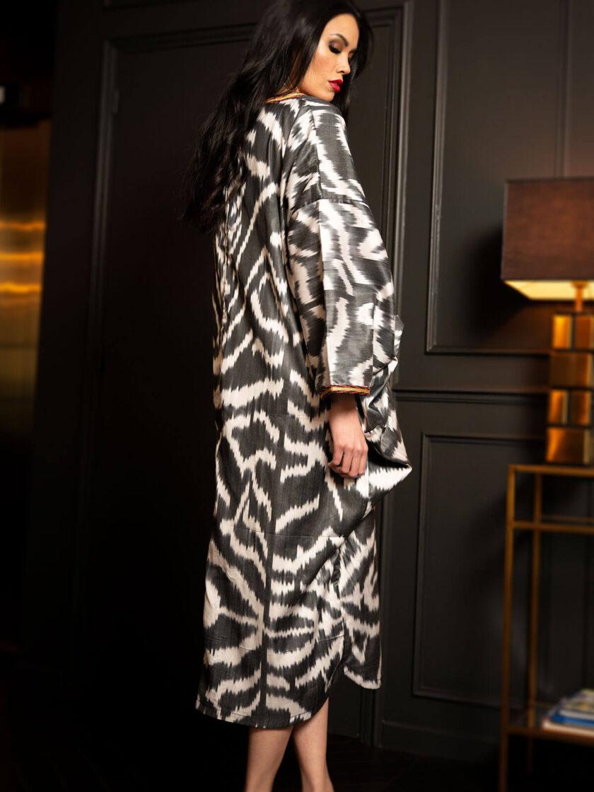 Frau mit langen schwarzen Haaren trägt einen Seiden-Kaftan mit schwarz-weissen Ikat-Muster