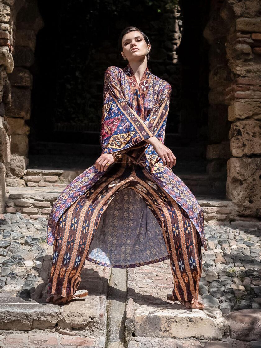 Junge Frau auf einem Fels stehend, in einem knielangen Kimono und weiter Hose mit armenischen Mustern aus der Mairik Kollektion von Belle Ikat