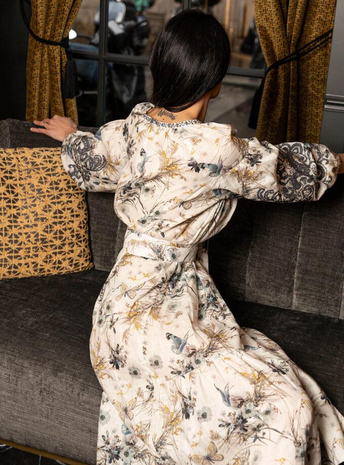 junge Frau im knielangen Leinenkleid mit Print aus Schmetterling-Mustern sitzt mit dem Rücken auf einer Couch