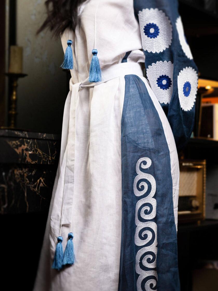 ein Ausschnitt von einem langen weiss-blauen Leinenkleid mit Stickereien