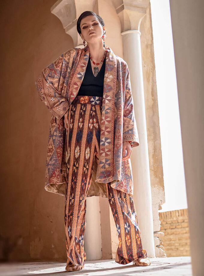 Junge Frau in einem knielangen Mantel und weiter Hose mit armenischen Mustern aus der Mairik Kollektion von Belle Ikat