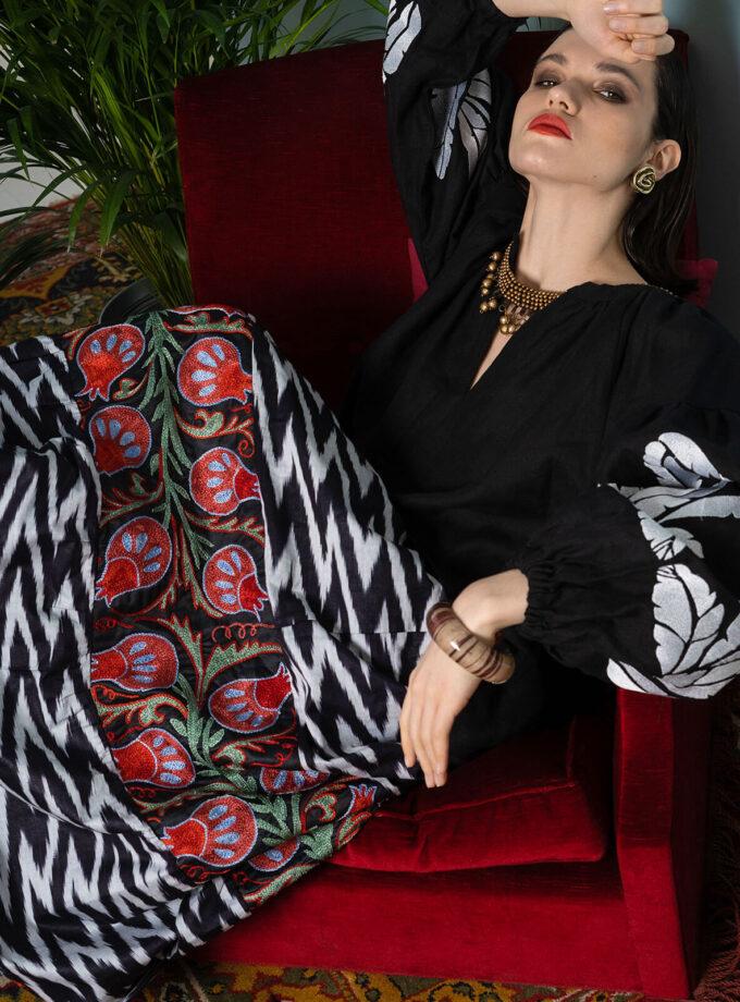 Eine Frau im langen Rock mit bunter Suzani-Stickerei sitzt auf einem roten Sessel
