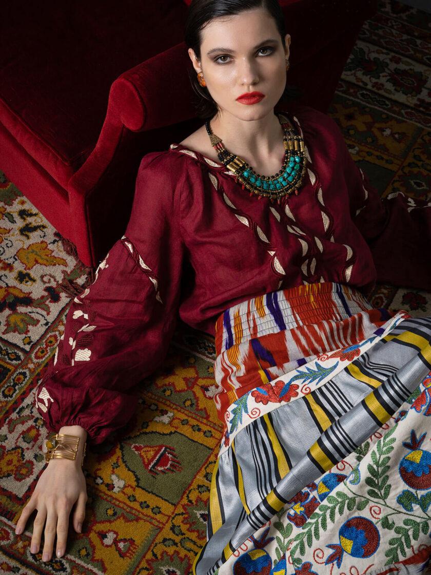 Eine Frau im langen Rock mit bunter Suzani-Stickerei liegt auf einem Teppich, mit dem Rücken angelehnt an einem roten Sessel
