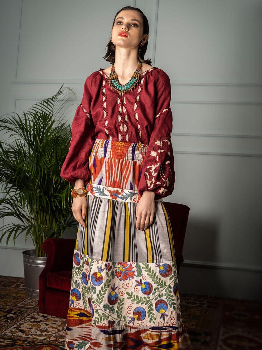 Eine Frau im bodenlanger Maxi-Rock aus Ikat-Seide und Baumwolle mit bunter Suzani-Stickerei