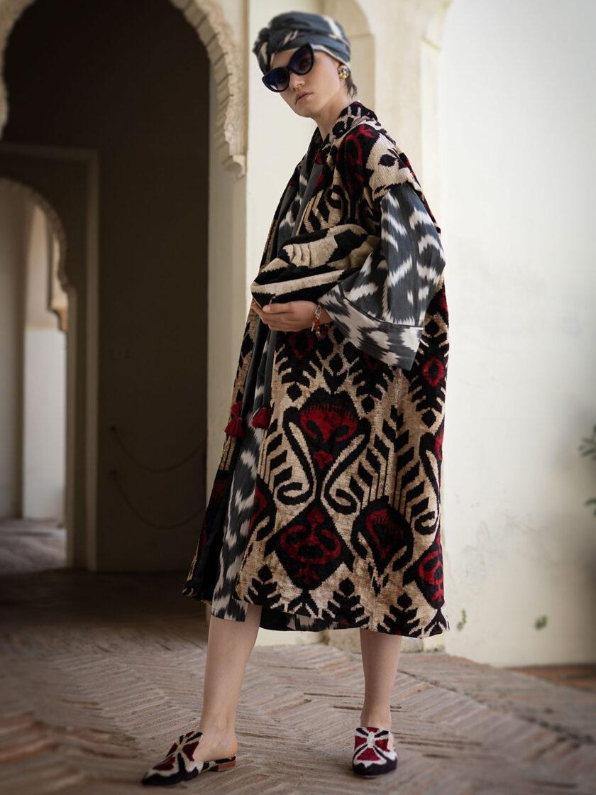eine junge Frau im Turban und einer langen Weste aus Seidensamt in rubinrot-schwarz