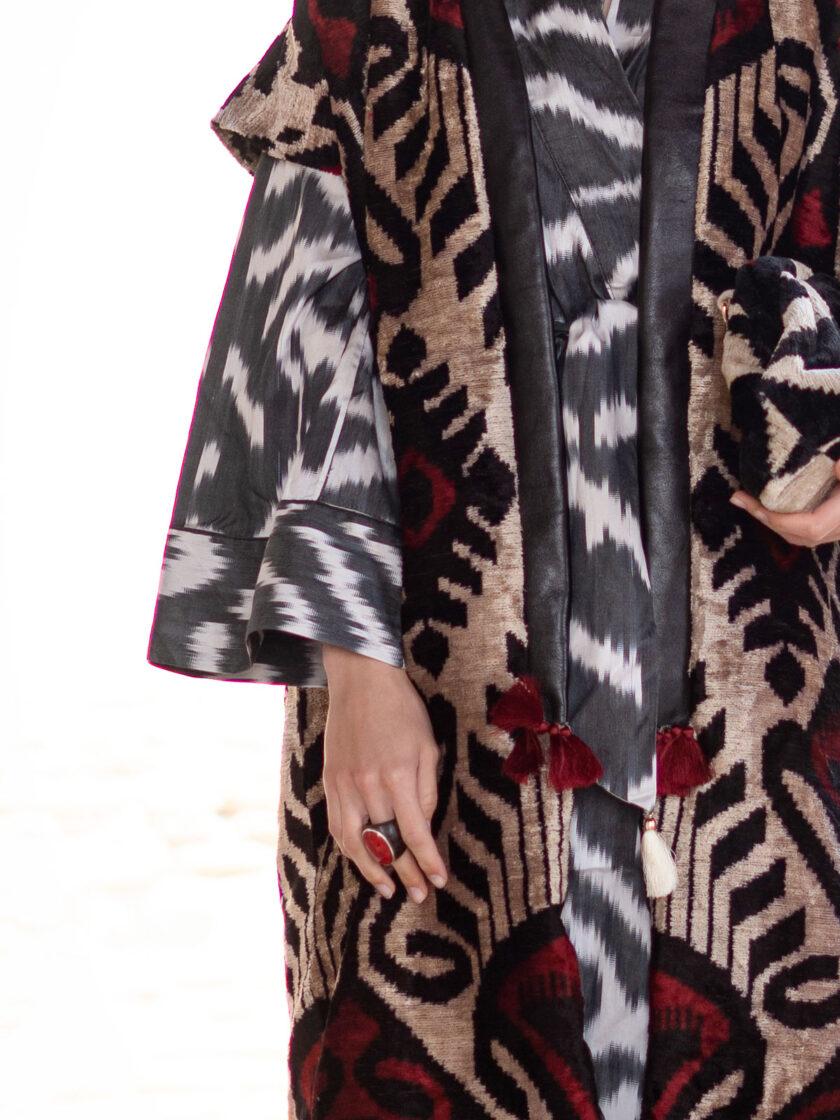 ein Ausschnitt einer langen Weste aus Seidensamt in rubinrot-schwarz