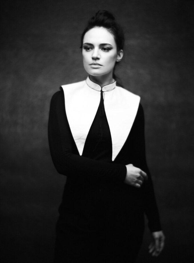 ein schwarz-weiss Portrait von einer Frau im dunklen Kleid mit weißem Kragen in gothic-chic