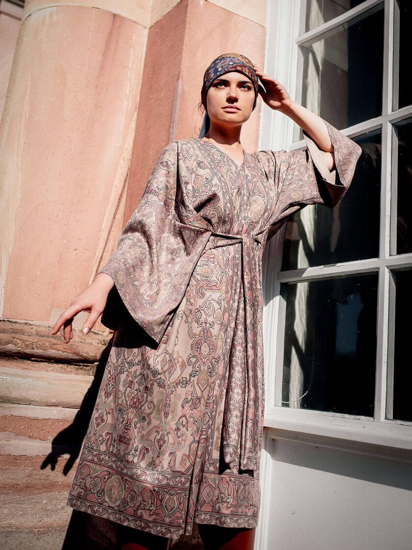 junge Frau steht draussen angelehnt an ein Fenster in einem knielangen Kleid in Wildlederoptik mit armenischen Mustern