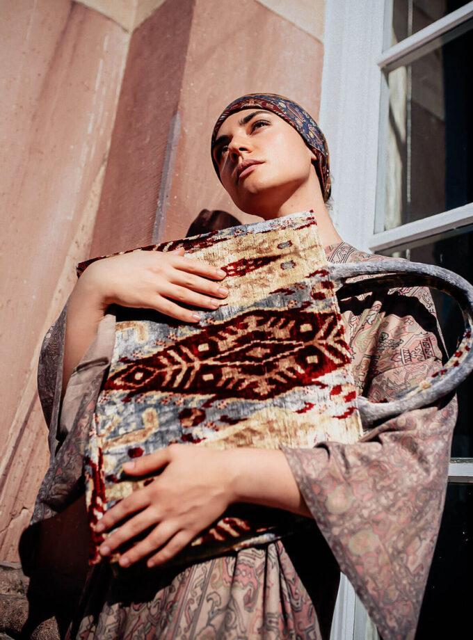 junge Frau hält eine gemusterte Tote bag in den Handen