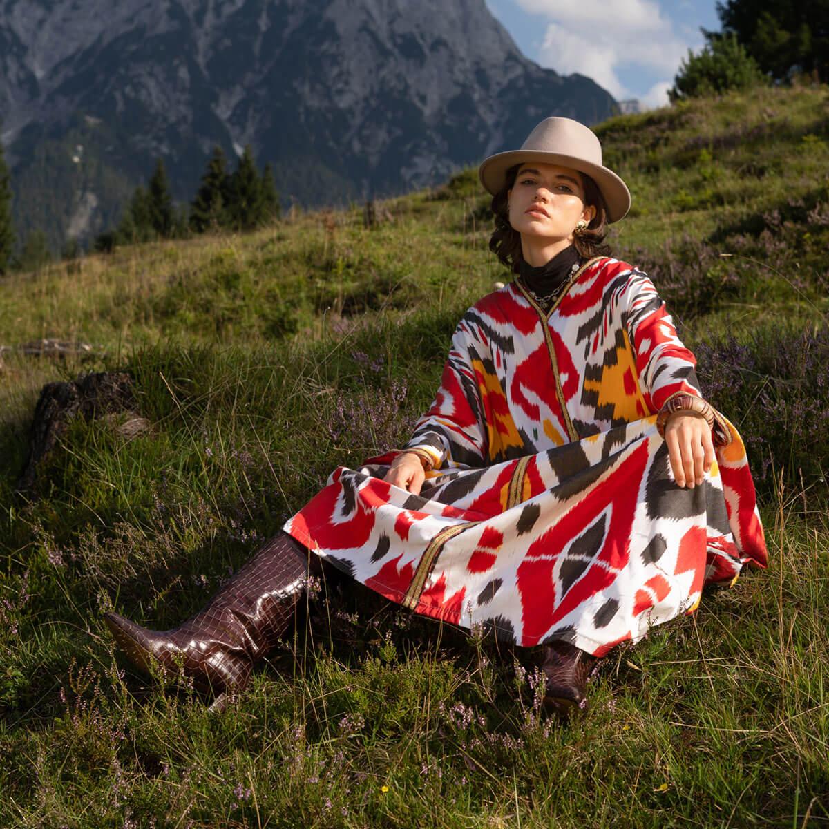 Junge Frau im Hut, braunen Stiefeln und einem buntem oversized Kaftan mit Ikat Mustern sitzt auf einer Wiese im Hintergrund sind Berge