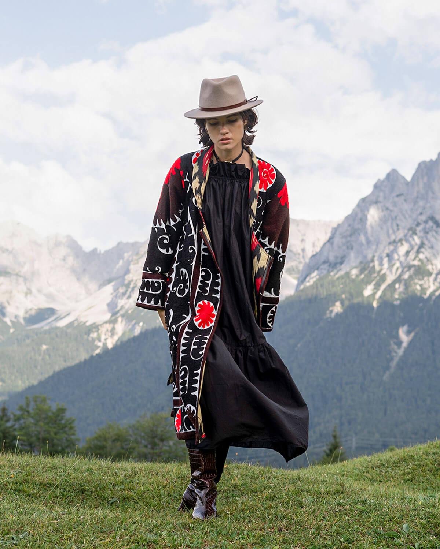 Berglandschaft mit junger Frau im Hut und einem schwarz-weiss-roten oversized Mantel mit Suzani-Stickereien