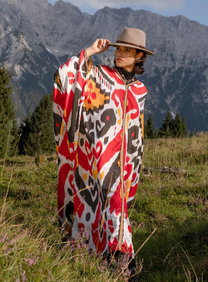 Berglandschaft mit junger Frau im Hut und einem buntem oversized Kaftan mit Ikat Mustern