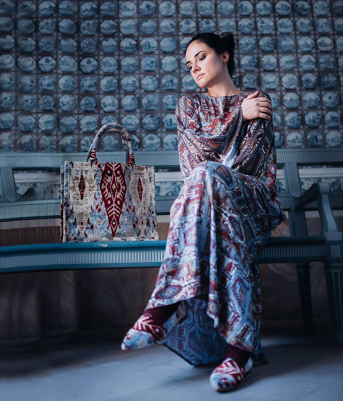 junge Frau sitzt auf einer Bank mit einer gemusterten Tote bag und Maxi Kleid mit armenischen Mustern
