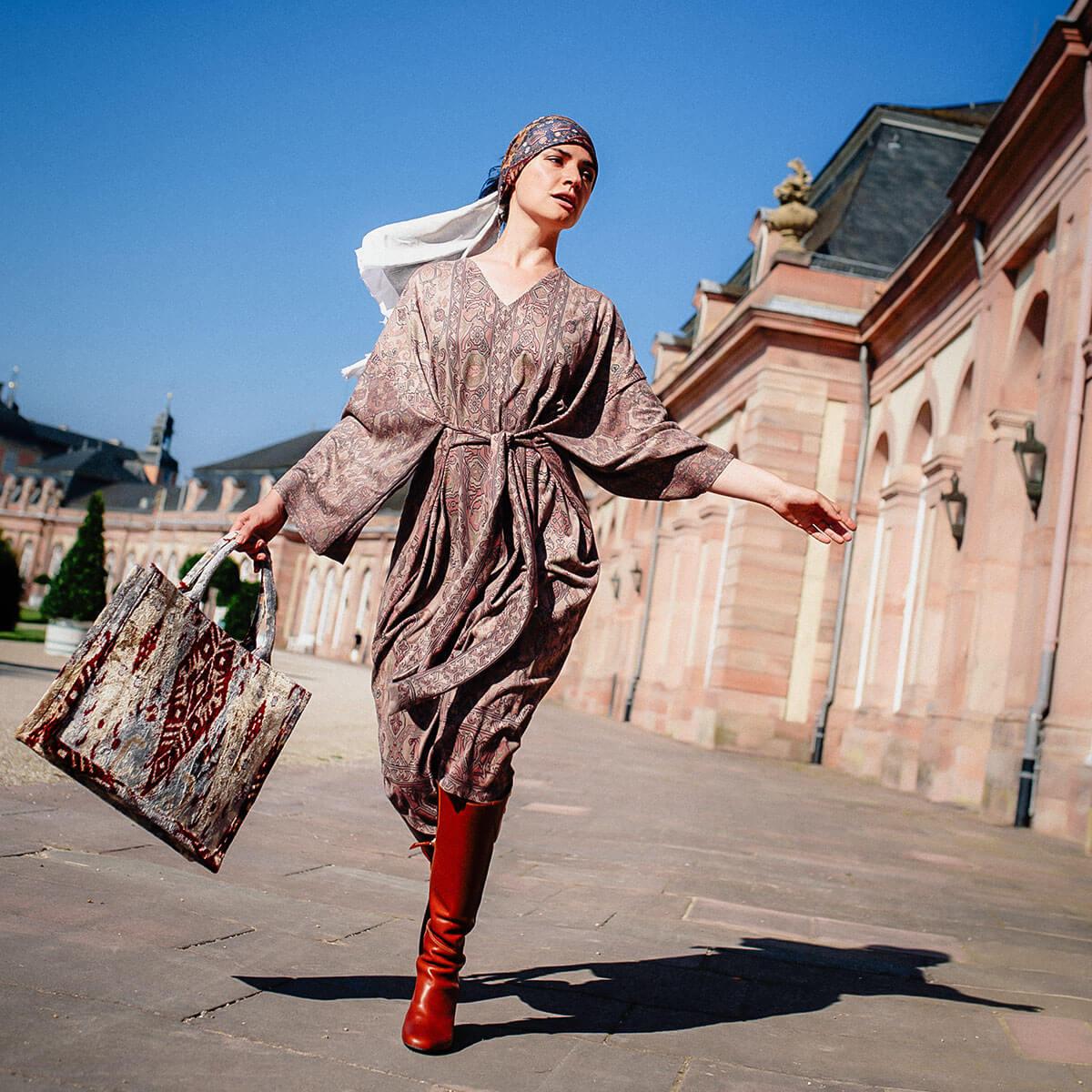 junge Frau läuft durch die Straße mit einer gemusterten Tote bag in der Hand und einem knielangen Kleid in Wildlederoptik mit armenischen Mustern