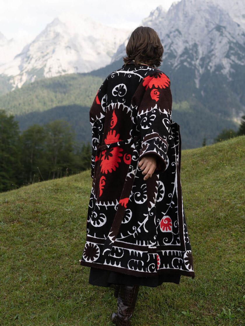 Berglandschaft und Rückenansicht einer jungen Frau in einem schwarz-weiss-roten oversized Mantel mit Suzani-Stickereien