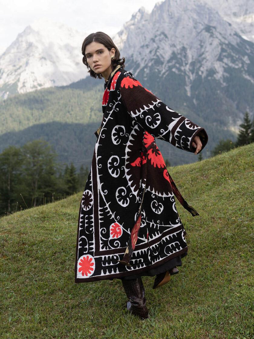 Berglandschaft mit junger Frau in einem schwarz-roten oversized Mantel mit Suzani-Stickereien