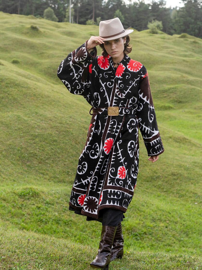 Grüne Landschaft mit junger Frau im Hut und einem schwarz-weiss-roten oversized Mantel mit Suzani-Stickereien